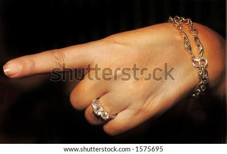 elegant ladies hand pointing left. - stock photo