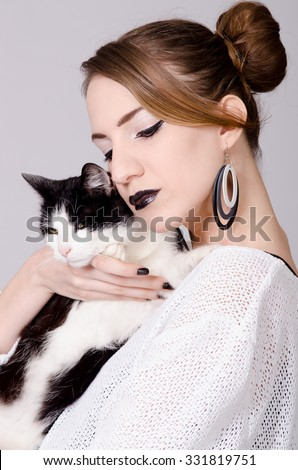 Elegant lady holding black and white cat with yellow eyes.