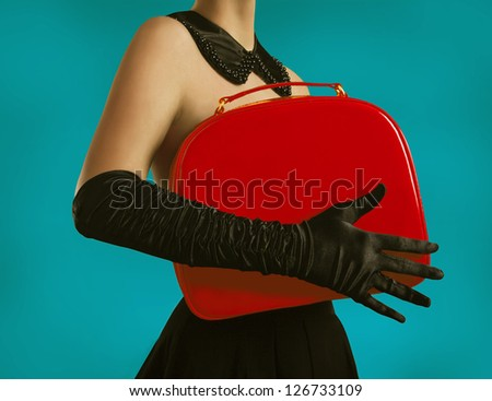 Elegant lady in gloves holding a red bag - stock photo