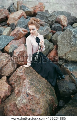 Elegant lady near the sea. Beautiful woman with stylish makeup is holing pearl necklace in her hand. She is sitting on the stone with her elegant blouse and long black skirt