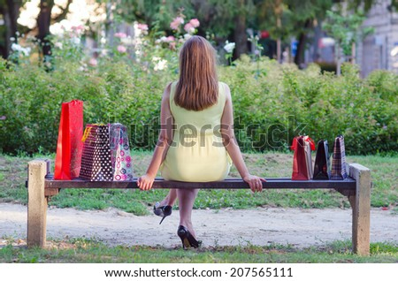 Elegant lady sitting in the park after shopping on sunny summer day. - stock photo