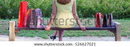 Elegant lady sitting in the park after shopping on sunny summer day.