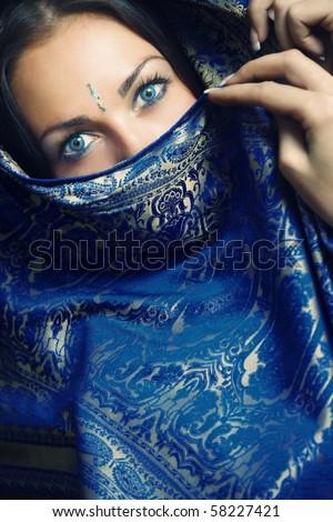 Elegant lady with blue eye lens in traditional Indian sari - stock photo