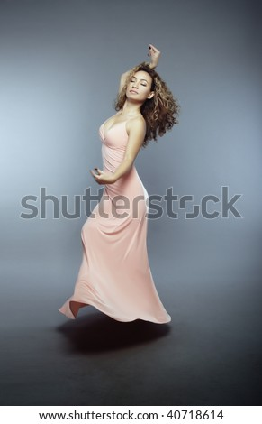 Elegant lady with closed eye dancing over the floor on a gray background - stock photo