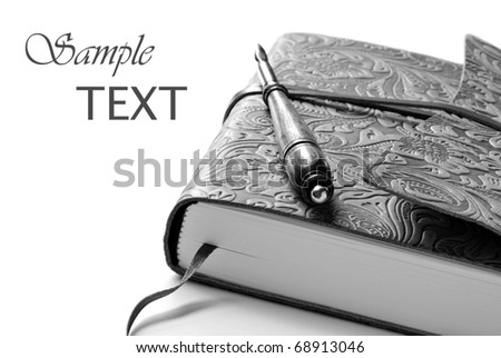 Elegant leather journal with calligraphy pen. Black and white macro with shallow dof and copy space. - stock photo