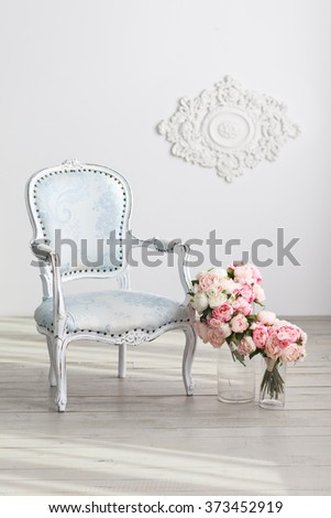 Elegant light-blue arm-chair and tender flowers near white wall. Interior in white colors - stock photo