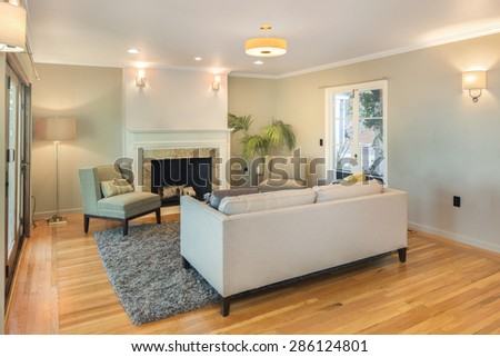 Elegant Living room with couch, french doors and fire place. Living room interior with copy space for art with hand-woven natural colored fine sisal rug open space living room within nature. - stock photo