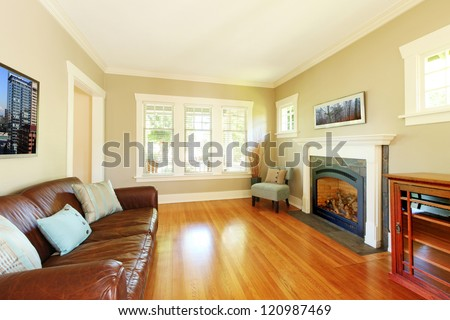 Elegant living room with fireplace and leather sofa with cherry hardwood floor. - stock photo
