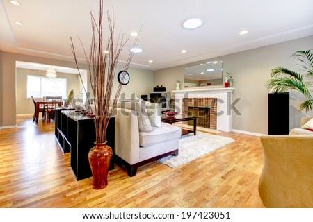 Elegant living room with fireplace, white couch and white soft rug. Room decorated with vase and dry branches. - stock photo