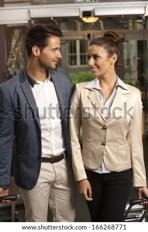 Elegant loving couple arriving at hotel lobby with suitcases, smiling. - stock photo