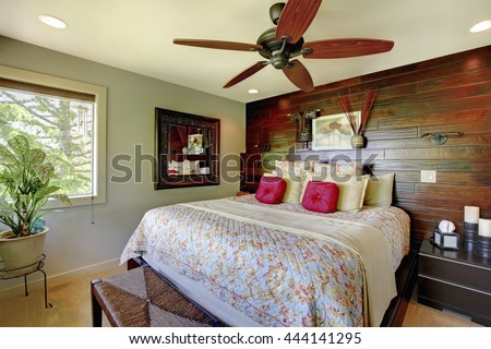 Elegant luxury master bedroom with wooden accent wall.  Nicely decorated interior design.