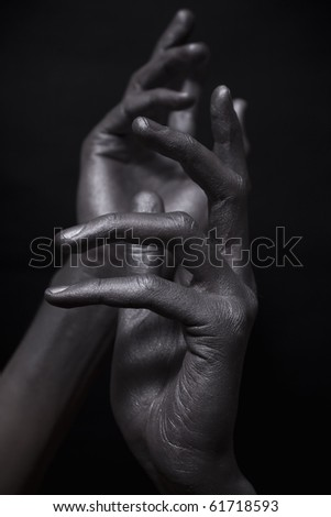 elegant male hands in silver paint on black background
