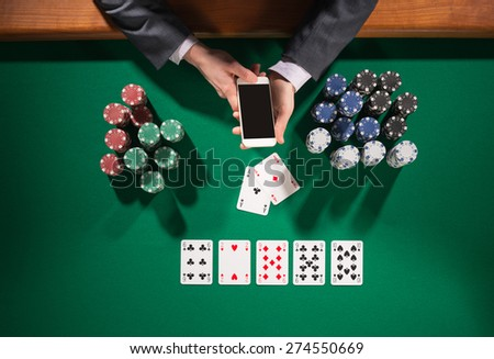 Elegant male poker player using a smartphone, cards and chips stacks all around, green table top view - stock photo