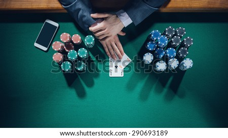 Elegant male poker player with smartphone holding two aces with stacks of chips all around, hands detail top view - stock photo