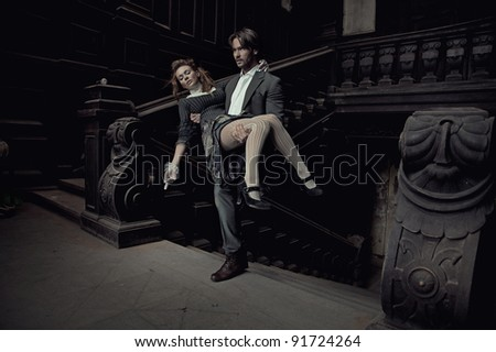 Elegant man carrying a beautiful brunette - stock photo