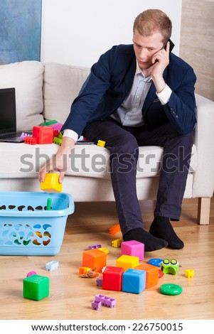 Elegant man cleaning up toys while talking on the phone