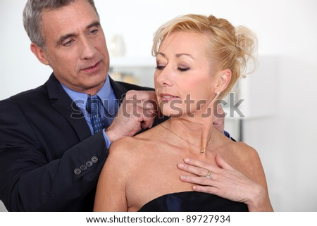 Elegant man closing the necklace of his wife - stock photo