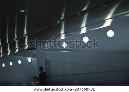 Elegant man descending on escalator after work - stock photo