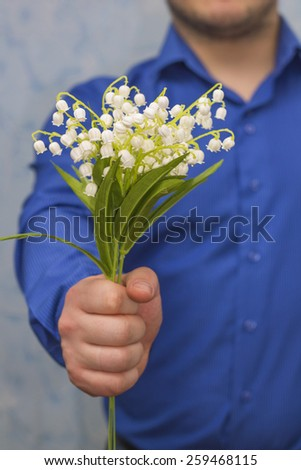Elegant man giving bouquet of spring flowers, close-up - stock photo
