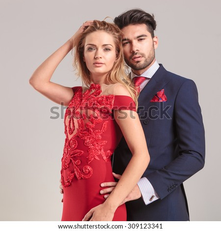 Elegant man holding his wife while she is fixing her hair. - stock photo