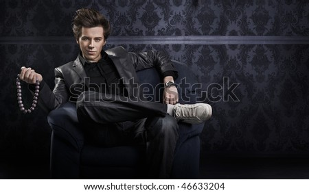 Elegant man holding necklace - stock photo