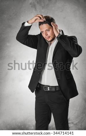 Elegant man in dark suit combing his hair - stock photo