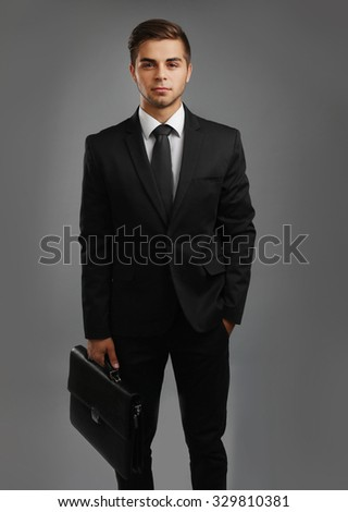 Elegant man in suit with briefcase on gray background - stock photo