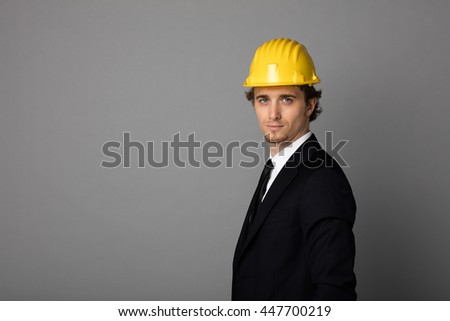 elegant man in suit with yellow protection helmet on gray background with empty space
