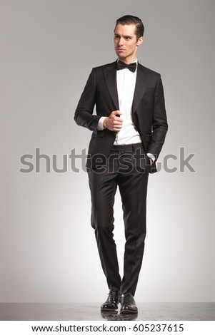 elegant man in tuxedo and bowtie looks away while holding his collar on grey studio background