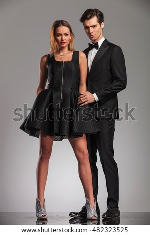 elegant man in tuxedo embracing his woman from behind, studio picture
