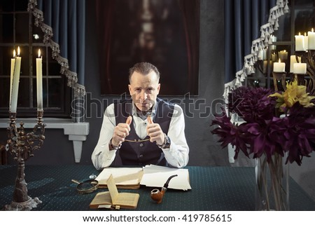 Elegant man is working creatively at the table with candles