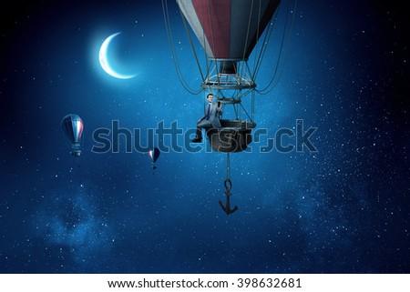 Elegant man traveling in aerostat - stock photo