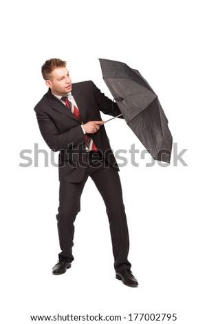 elegant man uses umbrella to protect himself on white background - stock photo