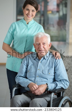 Elegant man using wheelchair and his kindly nurse - stock photo