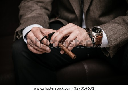 elegant man wearing suit and white shirt cut Cuban cigar indoor shot, closeup, selective focus