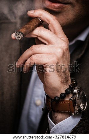 elegant man wearing suit and white shirt smoking  cigar indoor shot, closeup, selective focus - stock photo