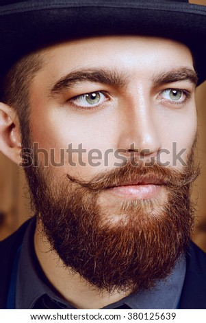 Elegant man with beard and mustache wearing suit and bowler hat. Old style fashion.  - stock photo