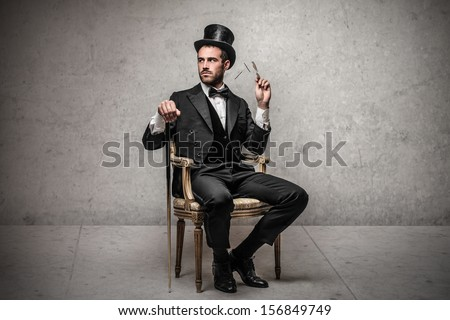 elegant man with cylinder sitting on a chair - stock photo