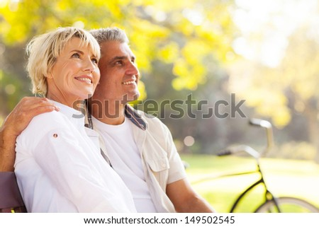 elegant mature couple sitting on a bench outdoors - stock photo