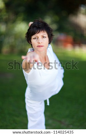 elegant mature woman doing yoga outdoors in forest - stock photo