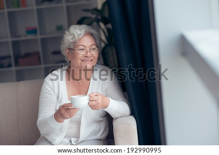 Elegant mature woman drinking coffee while sitting at window - stock photo