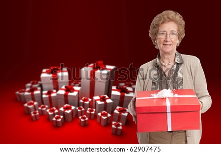 Elegant mature woman holding a present against a background full of gift boxes