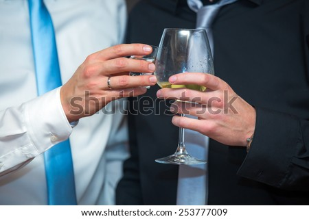 Elegant men in a business suit, holding glass of wine,