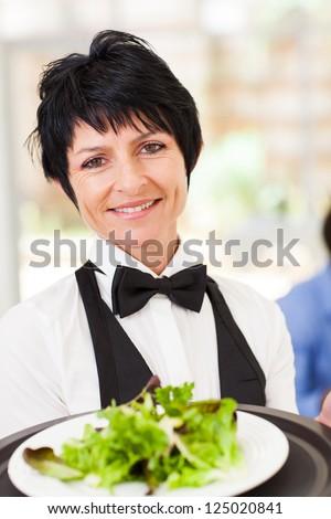 elegant mid age waitress serving salad in restaurant - stock photo