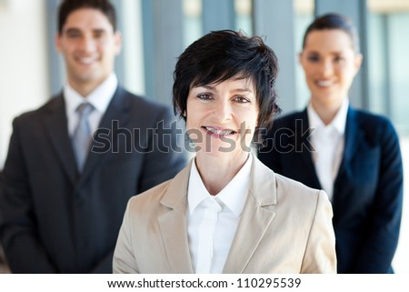 elegant middle aged businesswoman leader and team