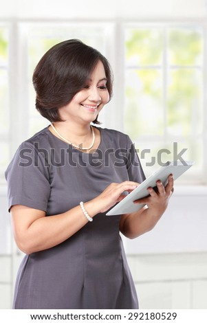 elegant middle aged businesswoman with tablet computer - stock photo