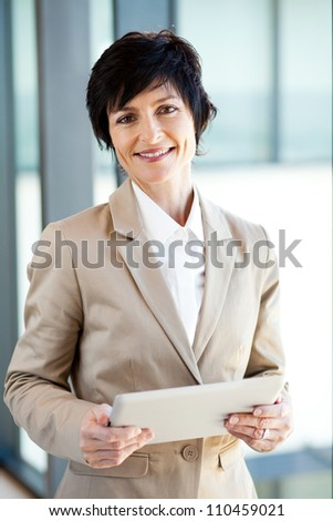 elegant middle aged businesswoman with tablet computer in office - stock photo