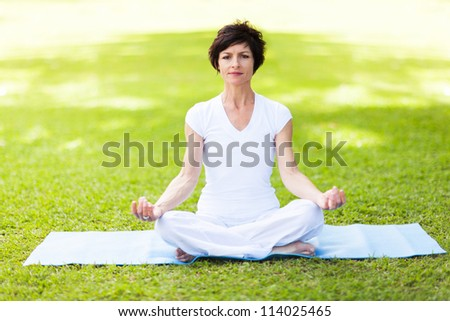 elegant middle aged woman doing yoga meditation - stock photo