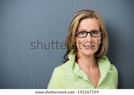 Elegant middle-aged woman in glasses looking directly at the camera with a friendly smile and interested expression, on grey with copyspace