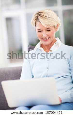 elegant middle aged woman using laptop computer at home - stock photo